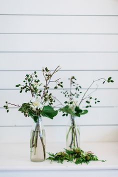 Glass bottles filled with natural flowers and foliage - Image by Therese Winberg Photography - A forest green wedding colour scheme at an intimate outdoor coastal ceremony in Finland with DIY wedding dress, flowers and stationery