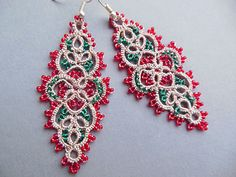 Tatted drop or dangle earrings in beige with red and green bead accents. Lightweight filigree pierced ear statement jewelry create a delicate accent for any occasion.  Original jewelry designs created with a small tatting shuttle and glass seed beads on strong thread. These hand tatted