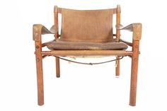 This gorgeous mid century Sirocco chair was designed by Arne Norell in 1964. The exposed Brazilian rosewood frame is constructed without any glue or screws and uses the support of slung leather.The beautiful original chocolate leather is perfectly patinated for a rustic, organic look. The design is accented by brass buckles and hooks. In excellent original condition with typical wear for its vintage.