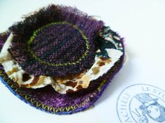 A brooch made of layers of different colored fabric
