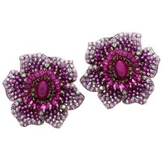 Crafted of 14-karat rose gold, these elegant floral earrings are set with rubies, pink sapphires and 1/2 carat of glittering diamonds. The earrings stay closed with secure leverback clasps.