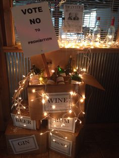 20's theme party idea!! Decorate used bottles with home made labels. Put in boxes with labels made from parchment paper. Add some shredded paper and white lights and you have a beautiful 20's party decoration!