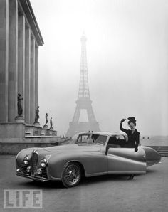 A model wearing a Jacques Fath ensemble poses beside a 1947 model Delahaye with the eiffel tower