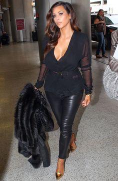 Kim Kardashian walks through Miami Airport wearing a low-cut blouse and clutching a fur coat