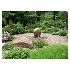 GAP Photos - Garden & Plant Picture Library - Dry gravel garden with urn water feature. Santolina neopolitana, Stachys byzantina and Grasses - GAP Photos - Specialising in horticultural photography