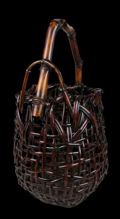 Flower arranging basket in an ovoid form with an angular branch bamboo handle. Woven of red-brown smoked bamboo. Signed on the reverse with an incised signature by the artist: Waichisai Saku or Made by Waichisai (Wada Waichisai III, 1899 – 1975). Early Shōwa era, circa 1930 – 1940.