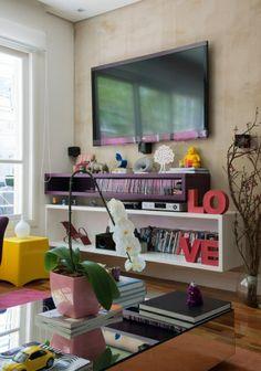 Esconde-esconde: A TV está afixada em uma parede de drywall, que esconde os fios dos aparelhos. A parede foi pintada com tinta que imita cimento queimado