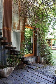 Patio rústico con revestimiento de chapa y escalera tipo flotante con troncos en una casa reciclada del Bajo San Isidro.