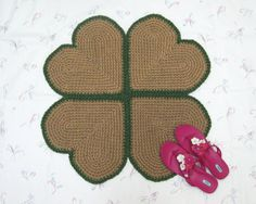 "Here's a handmade jute rug I created for St. Patrick's Day, shaped like a four leaf clover or shamrock, but it would look great year round. It's hand crocheted from all natural jute twine, trimmed in green, and measures about 29"" in diameter."