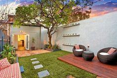 aménagement petit jardin dans l'arrière-cour avec fauteuils ronds en rotin, gazon artificiel et arbre