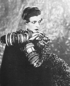 """Another profile of an """"unusual"""" rep of the flapper ideal: Nancy Cunard. She drank and drugged her way out of her inheritance, later marrying a Black man and writing a book on """"negro history."""" There is no denying the impact she had on future fashions, particularly in the drag/cross dressing arena!(photo by Man Ray)"""