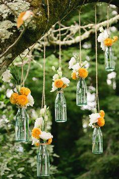 Vintage-Deko aus orangenen und weißen Blumen in hängenden Flaschen