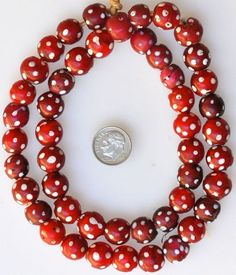 Venetian white heart eye beads 24 inch strand; bead size 12mm, variation of red hue Date: Late 1800s - early 1900s