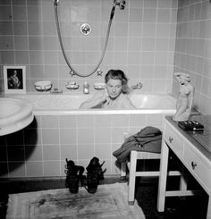 Lee Miller in Hitler's apartment at 16 Prinzregentlatz Note the combat boots on the bath mat now stained with the dust of Dachau; and a photograph of the previous owner of the flat propped on the edge of the tub. Published in UK Vogue, July 1945, page 73. Captioned as: Hitler's Munich apartment: Lee Miller, who scooped the story, luxuriates in Hitler's bath. - 1016 | LeeMiller