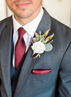 The Villa San Juan Capistrano Wedding Groom is Wearing a Charcoal Suit with Burgundy Tie and Pocket square.  Grey suit with white boutonniere for groom