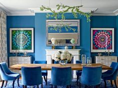In the dining room, the bejeweled branch chandelier and the hurricanes on the table are both by Tord Boontje in collaboration with Swarovski. The bespoke table by Whetstone Oak is surrounded by chairs dressed in a Dedar velvet. The butterfly artworks are by Damien Hirst, the mirror is by Louise Bradley, and the carpet is by Alexander McQueen for the Rug Company.