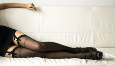 Long sexy Woman legs in black stockings on sofa, with high heels resting on sofa