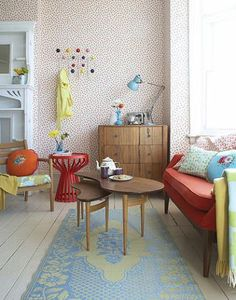 living rooms - sofa rug chair table stool lamp console wallpaper blue orange red yellow  yellow and blue rug, red sofa, vintage dresser chest,