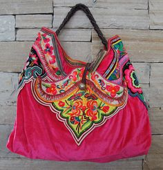 Oversized tote bag is unique, one-of-a-kind handcrafted fashion item created from vintage textiles from Southeast Asia. Both sides of bag feature bright pink velvet with hand embroidered textiles. Bag features short, fixed length, braided, dark brown leather shoulder straps, silver bobble top enclosure with two inside pockets (1 zippered) and key ring clasp inside. $390 includes FREE shipping.