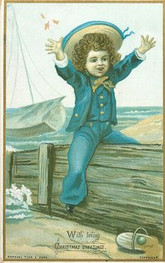 child in blue sailor suit straddles wooden fence at seashore, sailboat in distance