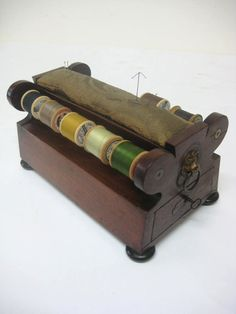Circa 1830, neat sized William IV cotton reel holder, with a shaped drawer on one side and lifting handles with lion mask faces, below two rods holding spools and a central pad for pins, all standing on 4 squat bun feet