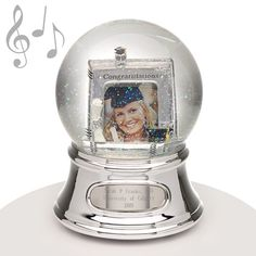 "Musical Water Globe - Graduation - This water globe features a frame inside the snowglobe for your special graduates picture along with the word ""Congratulations"" which makes it the perfect gift for your graduate. Appropriately, it plays the song ""Pomp and Circumstance."" They'll remember their grad forever with an engraved keepsake like this."