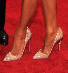Crystal-encrusted pumps with the requisite red sole (by this designer) help this life-size trophy sparkle.Who's wearing these pumps? | Whose signature red sole is this?