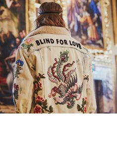Blind For Love, a phrase first introduced by creative director Alessandro Michele in French ('L'Aveugle Par Amour') for his first Gucci Cruise collection held in New York, appears on the back of a men's embroidered jacket featuring a dragon.