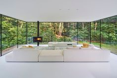 Inside this modern house, the floor and ceiling, as well as the furnishings have been kept bright, allowing natural light to reflect throughout the interior. #WhiteInterior #GlassWalls #ModernLivingRoom #Fireplace #Windows
