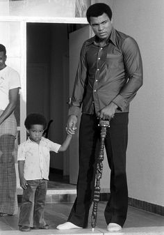 Four days before the fight, Muhammad Ali holds the hand of his son Ibn in Zaire.