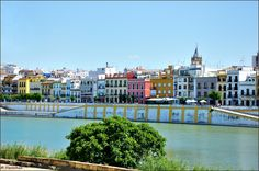 "El Barrio Triana y el Guadalquivir. --------------------------------------- We see Santa Ana Church --------------------------------------- Triana is one of eleven districts of Seville. It is traditionally known to be a district of artisans, specializing in particular the art of pottery and azulejos. It is also famous for its bullfighters (Juan Belmonte, Antonio Montes, Manuel ""Chicuelo"" Jimenez Moreno, ...), his singers and dancers of flamenco, which is considered the birthplace. ..."
