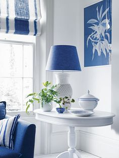 corner vignette in this living room with navy blue lamp shade, white oval side table, white and blue linen striped roman blind, white walls, navy blue sofa