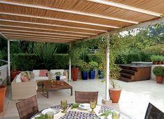 Sob a pérgola de ferro e bambu, a área de estar da família. A mesa tem louças e talheres da Roberto Simões e jogos americanos e guardanapos ...