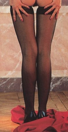 Black stockings and black heels by an undressing woman.