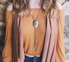 This Bolo Concho Necklace features a vintage style concho, two metal spacer beads, and two feather charms all attached to a 35 inch brown faux suede cord. This