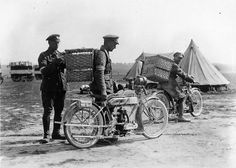 Two Scottish soldiers with motorbikes, each with a wicker basket strapped to his back. A third man is putting a pigeon in one of the baskets. In the background there are two mobile pigeon lofts and a number of tents.
