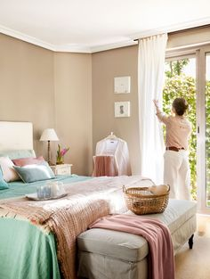 Mujer en dormitorio con pared arena y ropa de cama en rosa y azul descorriendo las cortinas blancas de la ventana_433522
