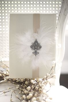 Feathers, satin ribbon, and medallion wrapping--perfect for a wedding gift