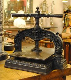 19th century cast iron book press with decorated with scroll and pan face.