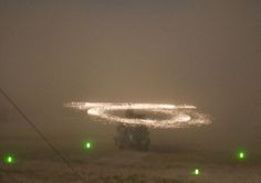 """the Kopp-Etchells Effect on a CH-47 Chinook Helicopter.   It is caused by sand hitting the titanium and nickel abrasion strips on rotor blades and eroding their surfaces. The cloud of tiny metal particles spontaneously ignites in the air (a """"pyrophoric oxidation of eroded particles""""), creating a visible corona.  Photo - Michael Yon"""
