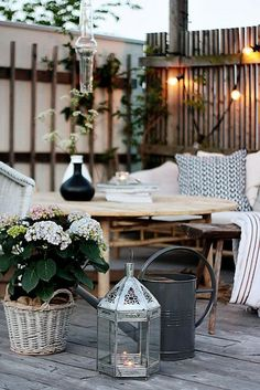 Summery patio garden with light toned textiles and wood, a silver lantern and string lights.