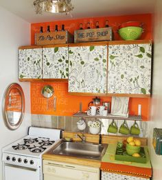 The orange really pops in this tiny kitchen.