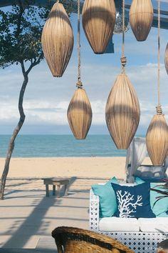 Lounge com luminárias em palha e sofá com almofadas à beira mar. Foto: Duo Borgatto