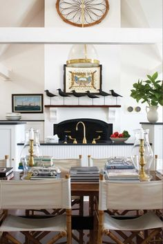 Open kitchen with vaulted ceiling, beams, brass accents, director's chairs, maritime painting