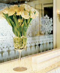 Brides: Crystal Ball :To cut costs, make your own showstopping flower arrangement. Start with a simple stem vase, and glue flat-back crystals in a circular pattern around its base. Create more sparkle by partially filling the vase with more crystals, then adding water and a bouquet of tulips.