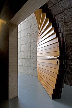Curtain Door by Matharoo Associates. The massive door is made of 40 sections of thick Burma teak and sits between the entrance's concrete walls. Each section has been carved to incorporate 160 pulleys, 80 ball bearings, one wire rope, and a hidden counterweight (2012)