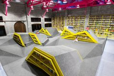"""Cool Bookish Places: Conarte Children's Library... Check out the kid in the upper right of the photo, the one sitting at the apex of one of the """"mountains."""" :-) It's so nice to see library patrons in pictures of a library, especially when that library is for children and the patrons are kids! :-)"""