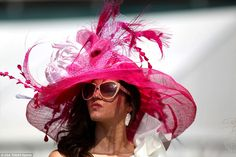 This attendee brought the glamour with a hot pink feathered hat and large baby pink sungla...