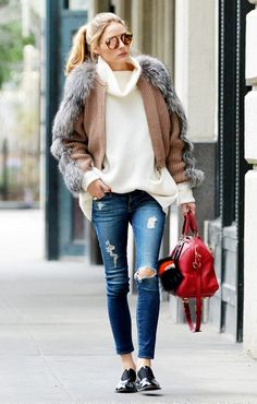 Olivia Palermo wears a cowl-neck sweater, fur-trimmed cardigan, distressed skinny jeans, red satchel, oxfords, and mirrored sunglasses