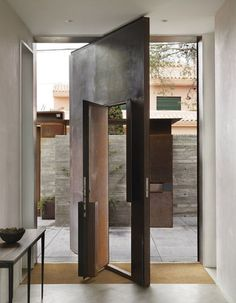 A doorway from a live/work project in Spain is another example of how Kundig makes kinetic parts of a house even more special by confounding expectations about how they work. A tall steel pivot door is inset with a pilot door, allowing for varying degrees of openness between the indoor and outdoor spaces. It also recalls the grand doors with smaller inset doors that can be found in church architecture.